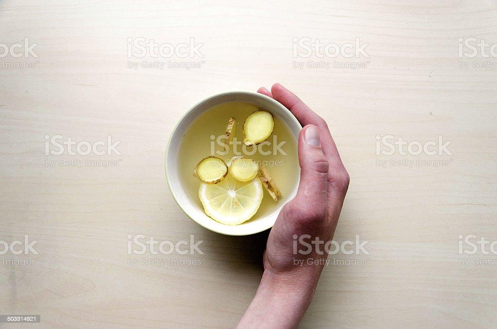 Lemon, cup of tea, light table, human hand. stock photo