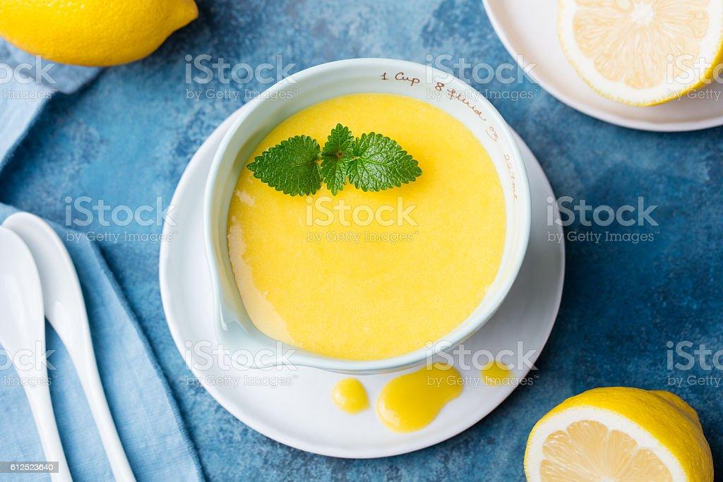 Lemon curd in glass with fresh lemons Blue stone background stock photo