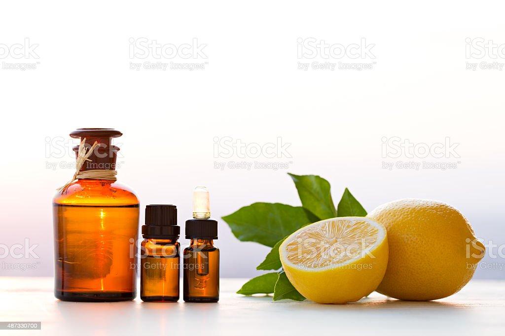 Lemon essential oils in bottles with lemon stock photo