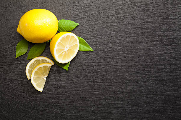 Lemon fruit on black slate background shot directly above stock photo