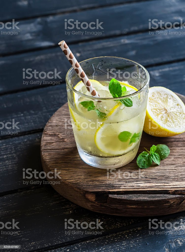 Lemon, ginger and mint lemonade on a wooden rustic board stock photo