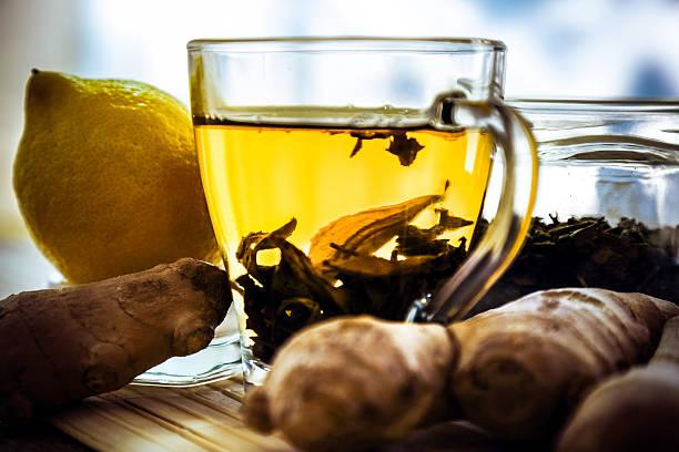 zitronensaft, ingwer wurzeln und teetasse auf tisch - grüner tee koffein stock-fotos und bilder