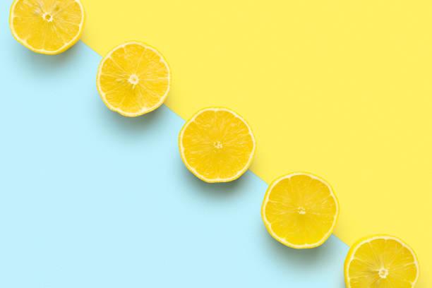 Zitronenhälften in der Reihe auf pastellgeltem und blauem Hintergrund. Minimales Sommerkonzept Flat lay. – Foto