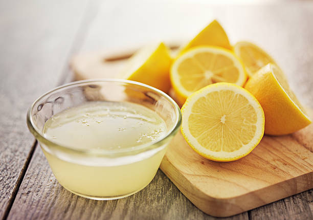 lemon juice freshly squeezed lemon juice in small bowl lemon juice stock pictures, royalty-free photos & images