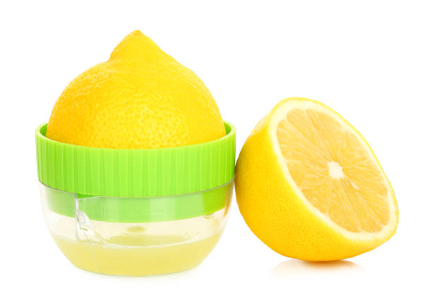 lemon juice lemon on small juicer and half a lemon isolated on white lemon juice stock pictures, royalty-free photos & images