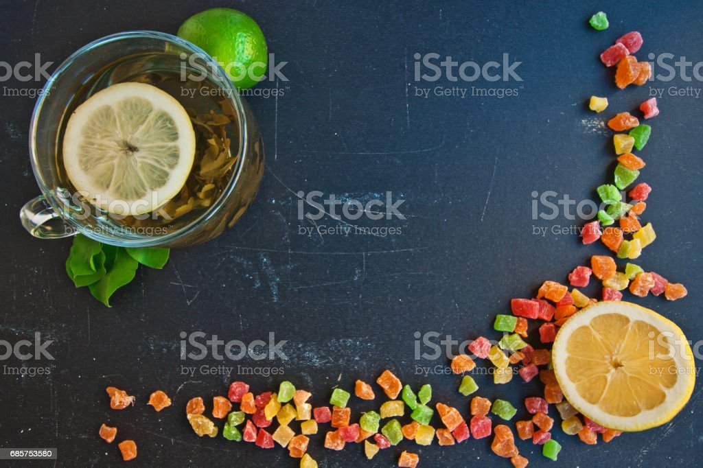 Lemon, lime, cup of tea and a few candied fruits on a black board foto stock royalty-free