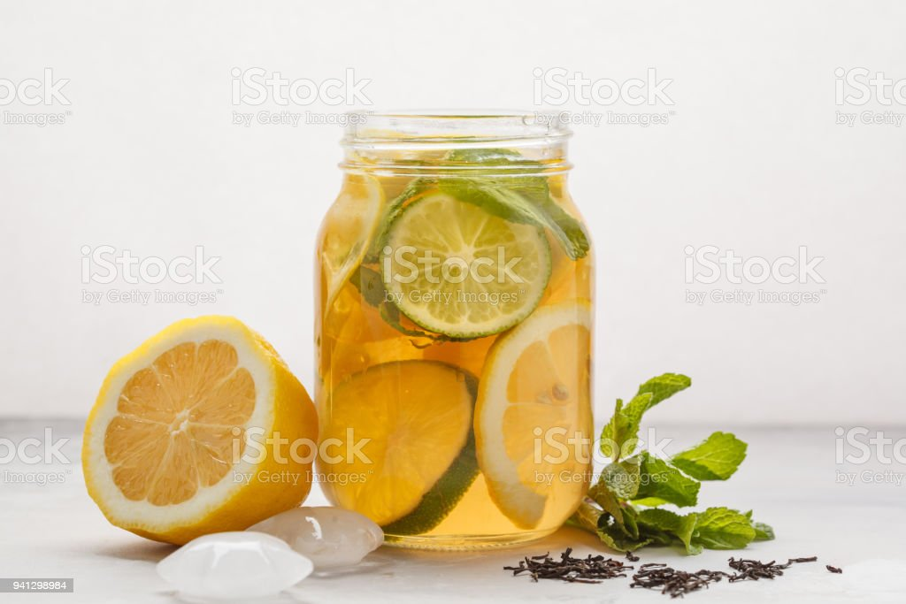 Lemon lime ice tea with mint in a glass jar, white background, copy space. Summer refreshing drink concept. stock photo