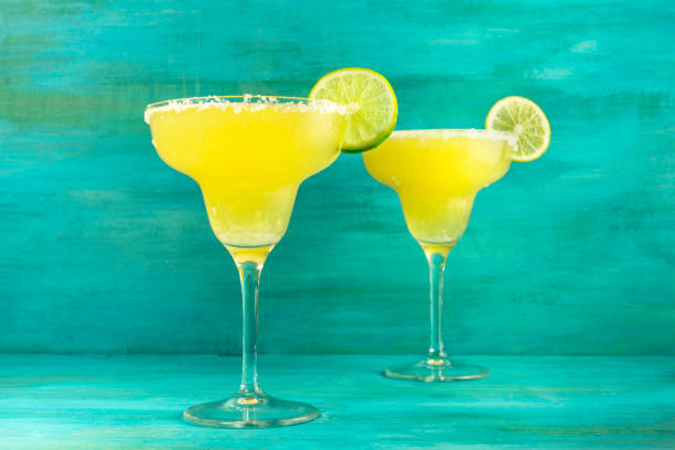 lemon margarita cocktails on vibrant turquoise with copyspace - margarita drink stock photos and pictures