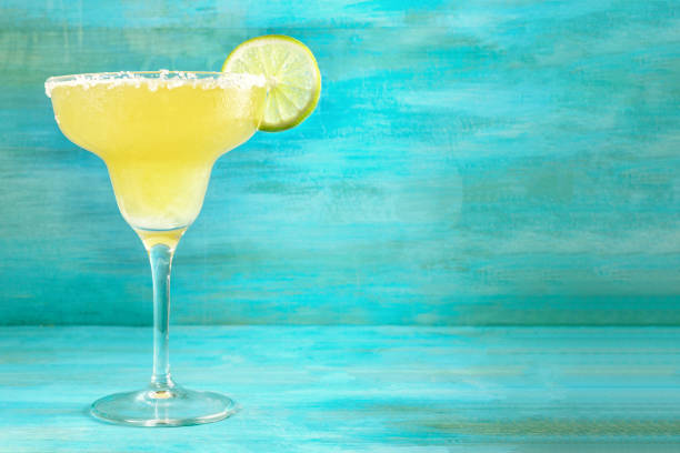 Lemon Margarita cocktails on vibrant turquoise with copyspace Lemon Margarita cocktail with a wedge of lime on a vibrant turquoise background with copy space margarita stock pictures, royalty-free photos & images