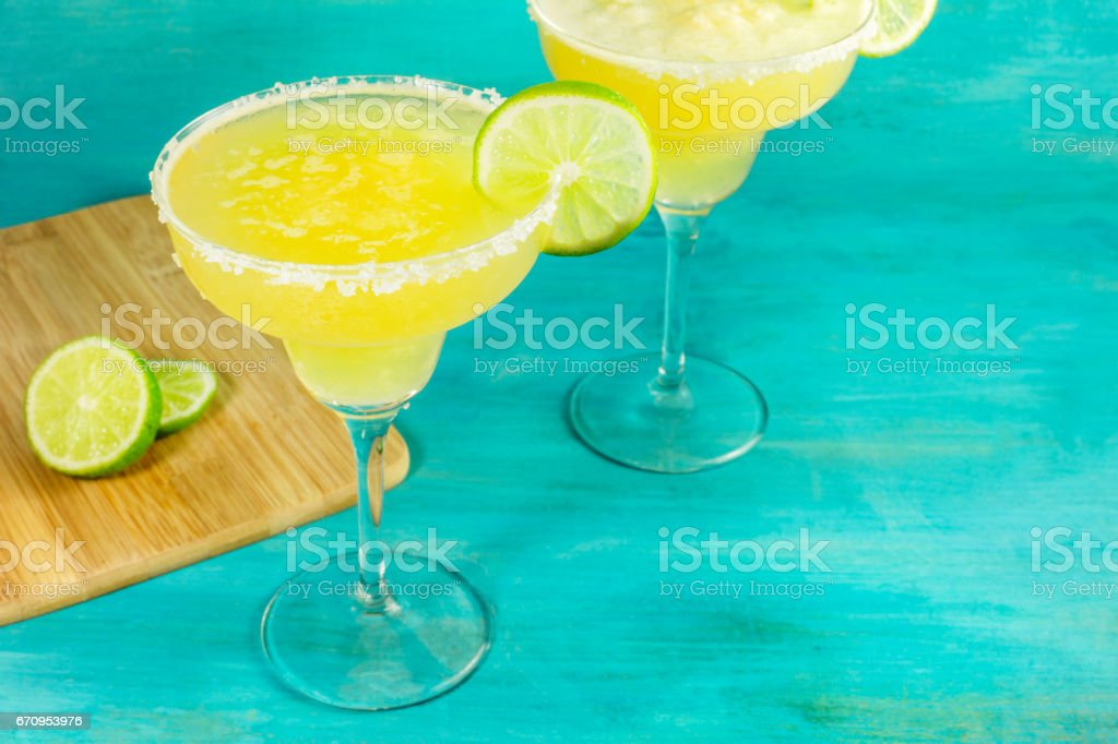 Lemon Margarita cocktails on vibrant turquoise with copyspace stock photo