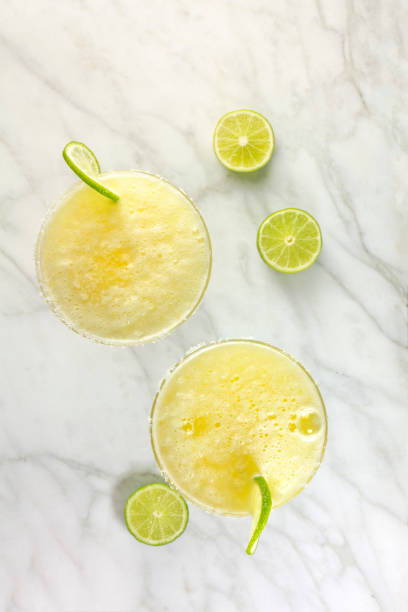 lemon margarita cocktails with limes and copy space - margarita drink stock photos and pictures
