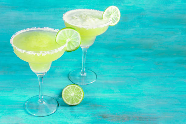Lemon Margaritas on vibrant blue with copy space, toned Lemon Margarita cocktails with wedges of lime on a teal background with copy space, toned image margarita stock pictures, royalty-free photos & images