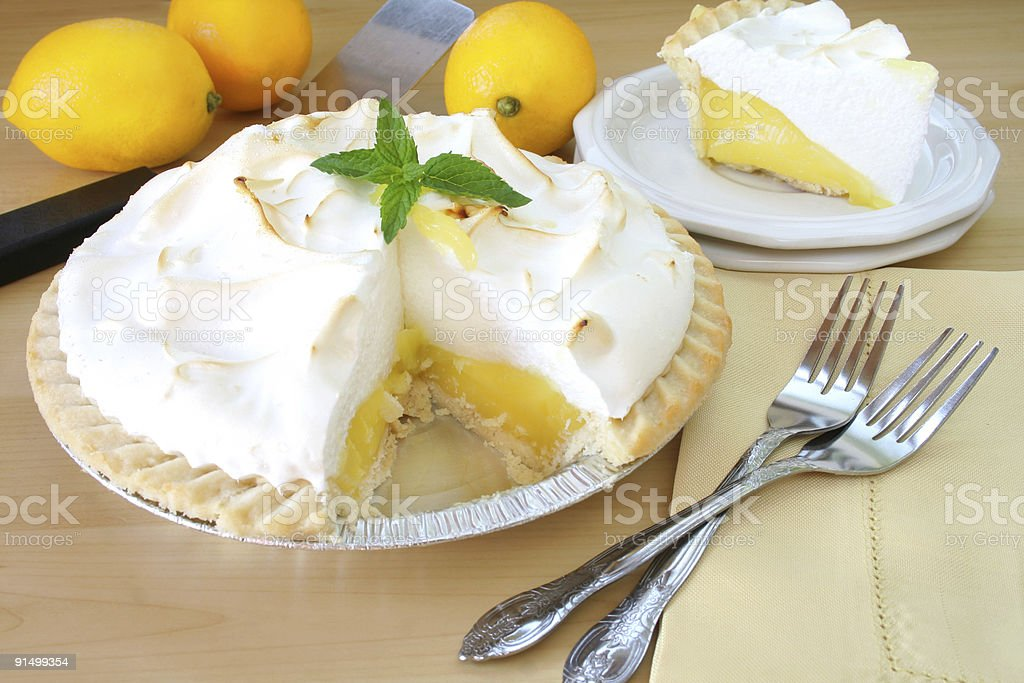 Lemon meringue pie with two forks on a table royalty-free stock photo