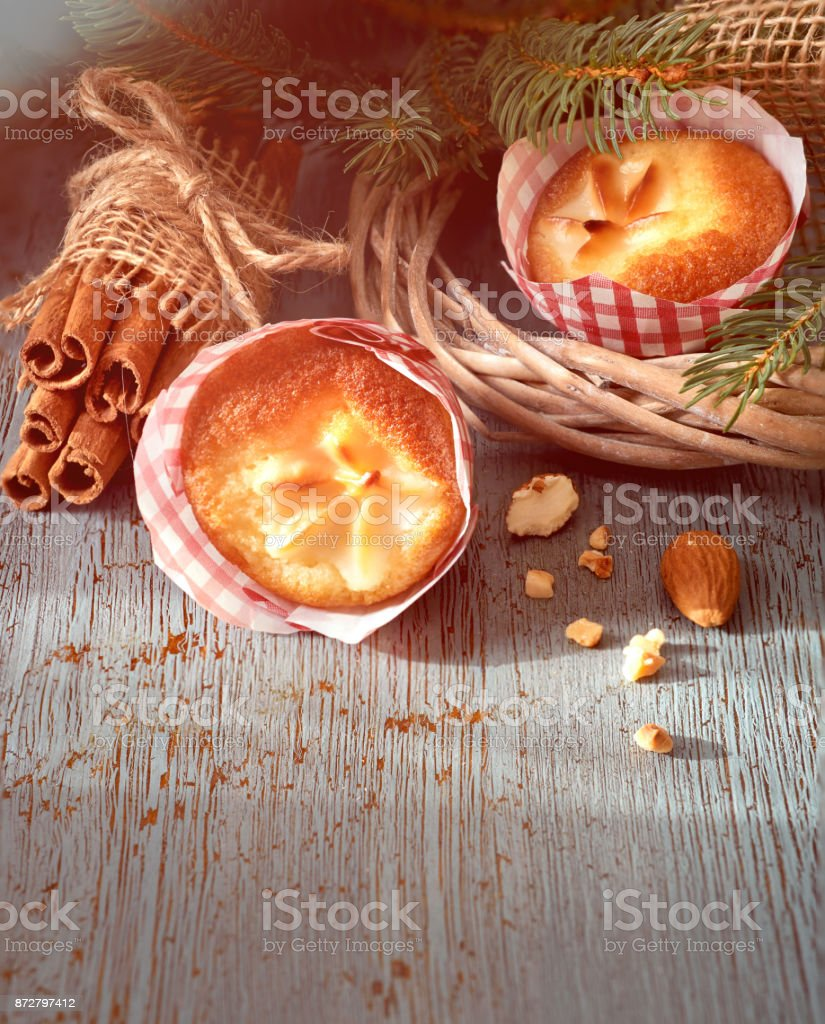 Lemon muffins on rustic wooden table with Christmas twigs, almonds and cinnamon sticks stock photo
