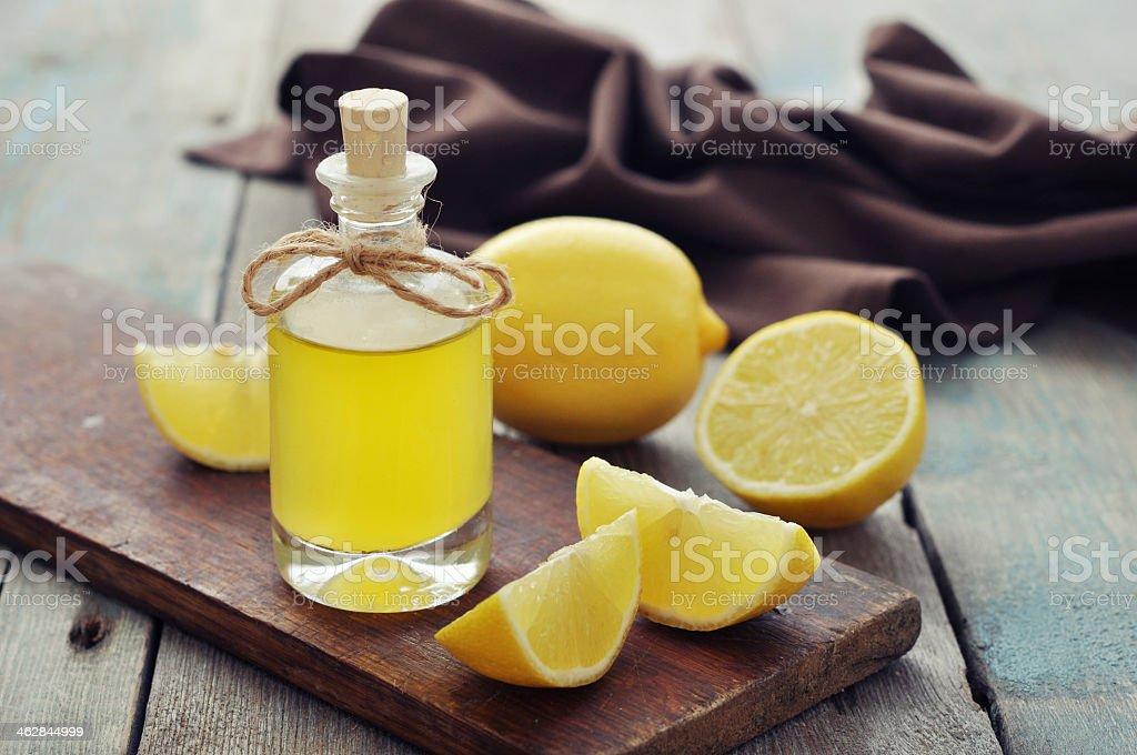 Lemon oil in a glass jar surrounded by lemons stock photo