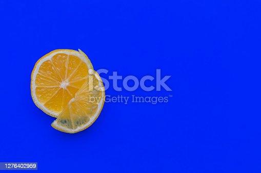 Lemon on a blue background. Citrus, vitamin C, fruits, lemon slice, detox. Flat lay, copy space, top view.