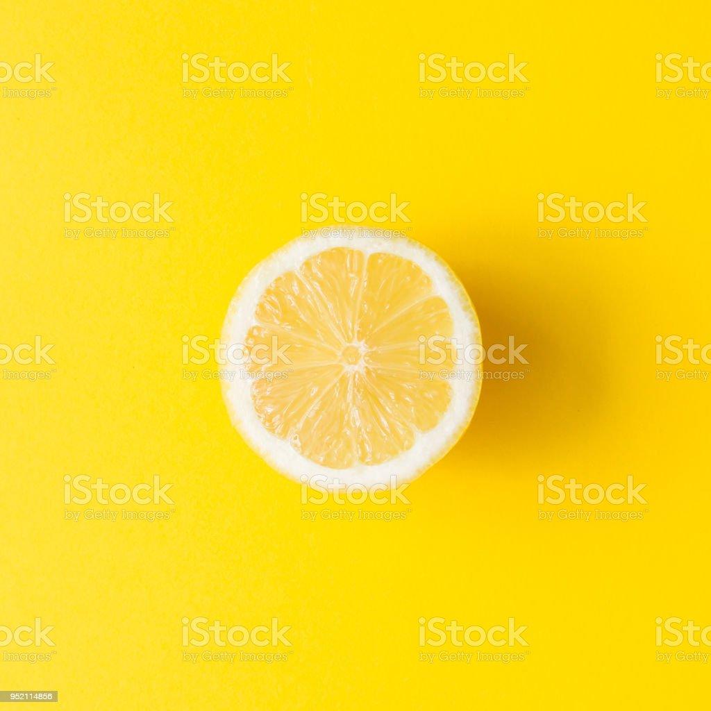 Lemon on vivid yellow background. Minimal summer concept. Flat lay. stock photo