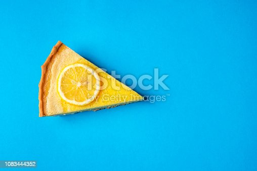 Slice of yellow lemon cake decorated with a slice of lemon, on a blue background. Directly above view. Minimalist style. Delicious fruit dessert.