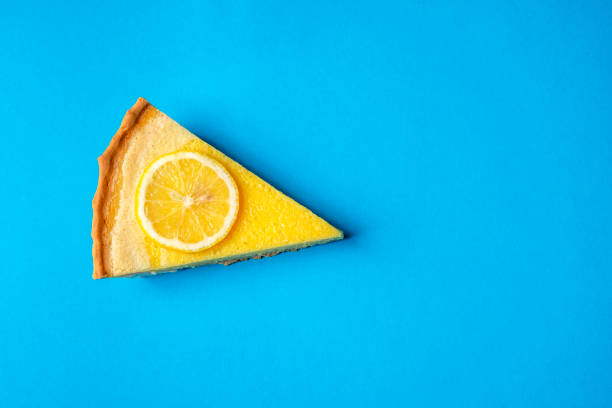 lemon pie slice on a blue background. above view and copy space - кусок торта стоковые фото и изображения