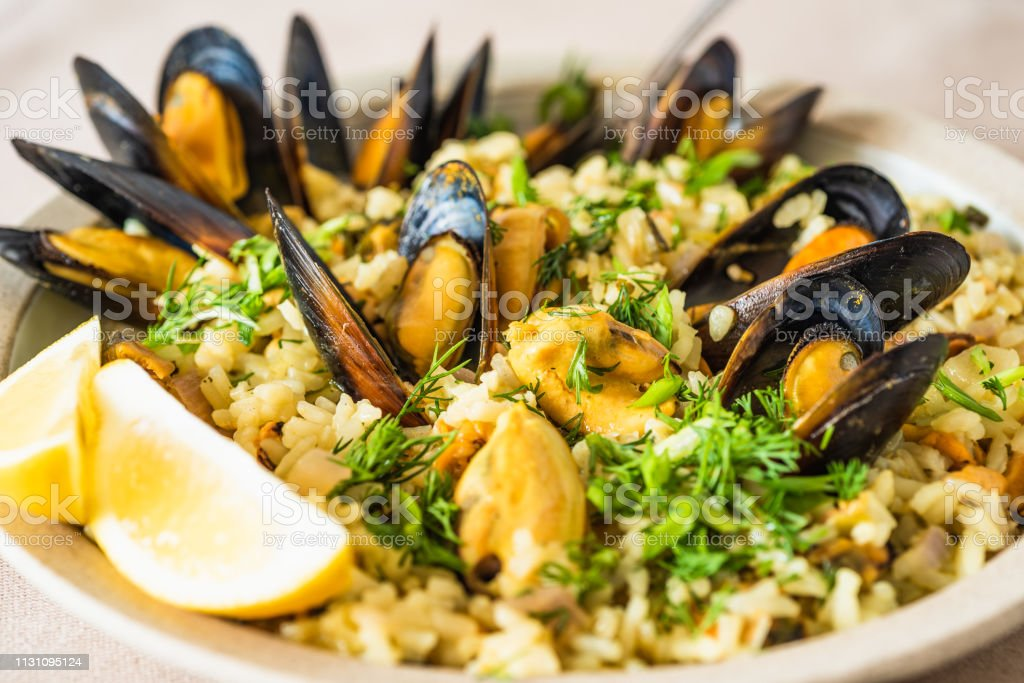 Lemon rice with mussels, midopilafo in a plate, closeup - a Greek dish