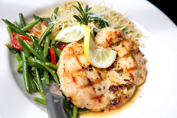 Lemon Rosemary Chicken On Plate Of Spaghetti And Green Beans A restaurant style plate of lemon rosemary chicken on a bed of steamed green beans and thin spaghetti topped with a lemon twist. main course stock pictures, royalty-free photos & images