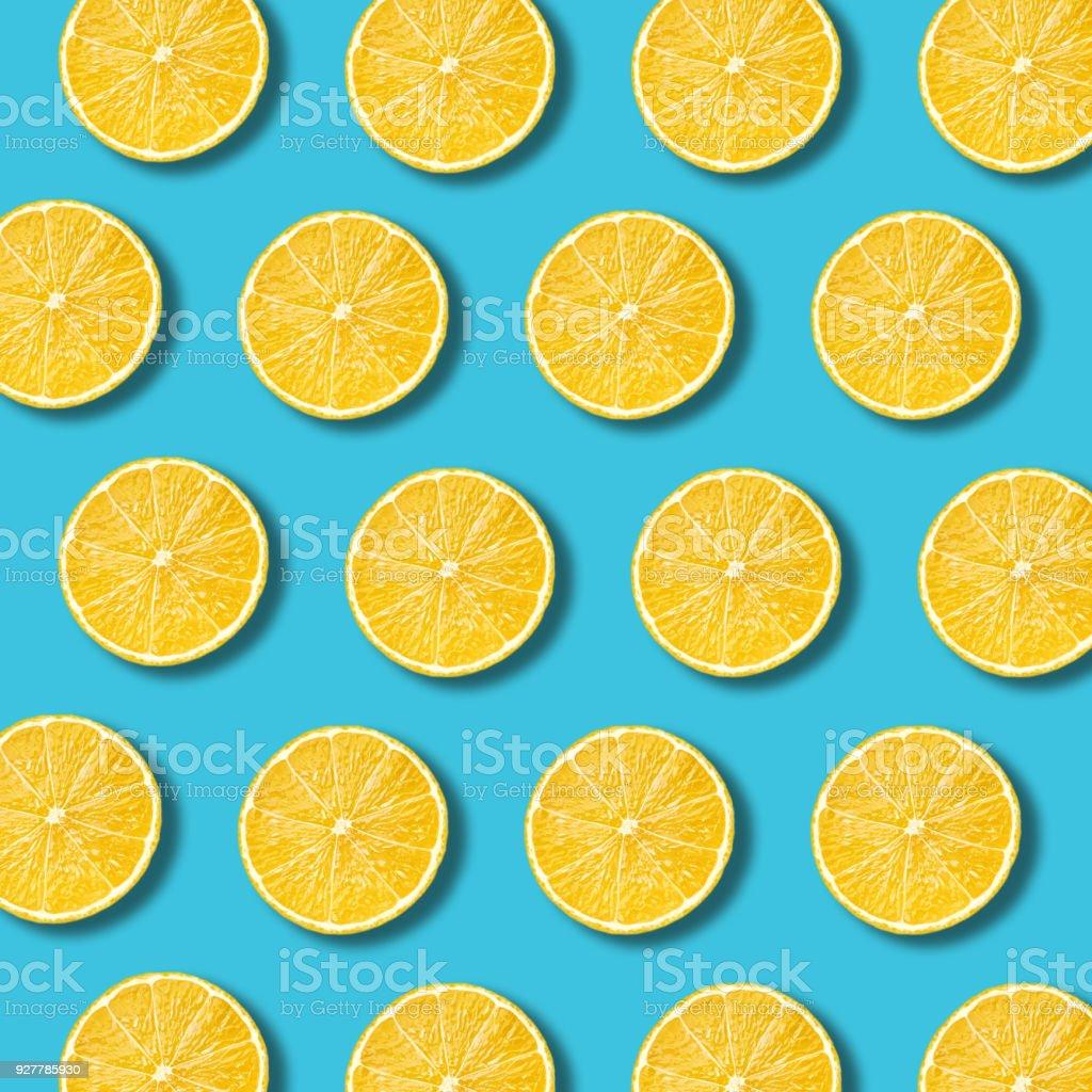Lemon slices pattern on vibrant turquoise color background stock photo