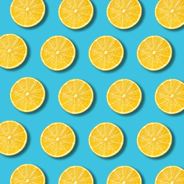 Lemon slices pattern on vibrant turquoise color background stock photo