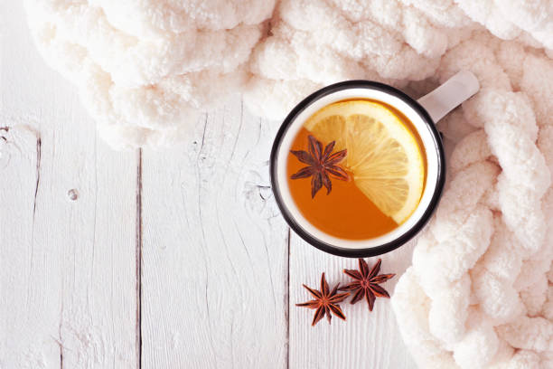 Lemon spice tea, top view on a white wood background with cozy blanket Lemon spice tea, top view on a white wood background with blanket. Cozy fall or winter theme. star anise stock pictures, royalty-free photos & images