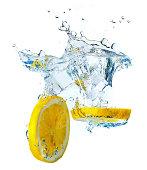 Lemon slices and ice cubes splashing water, isolated on white background