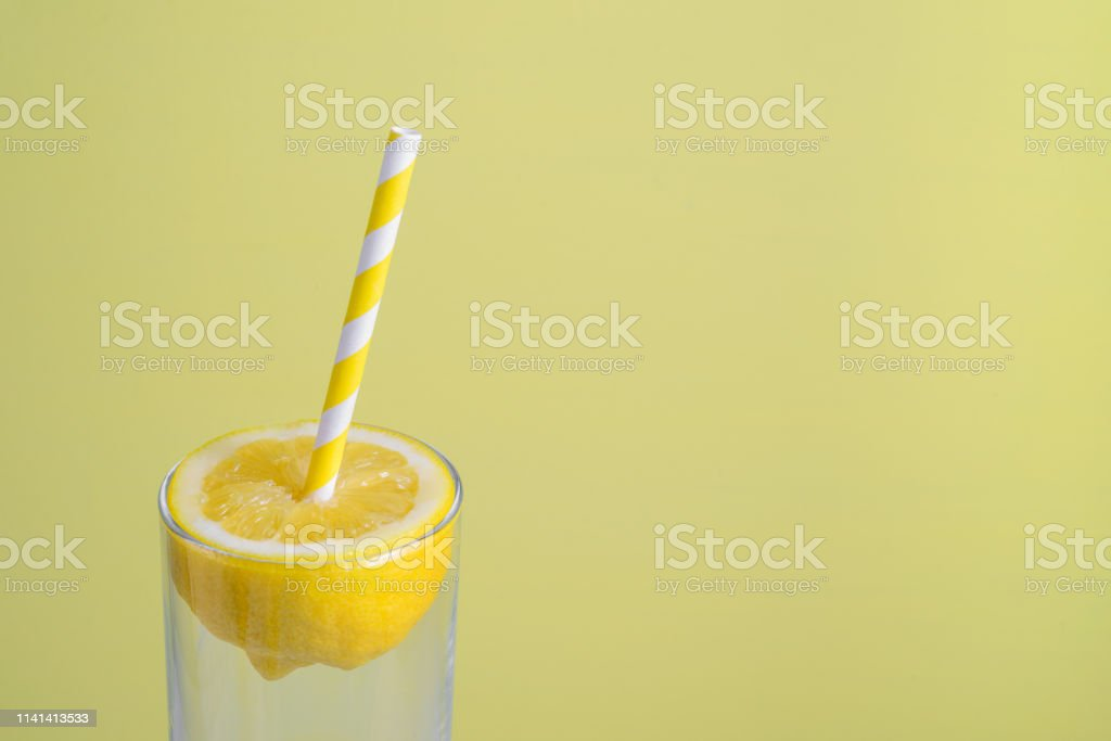 Lemon half with paper straw in glass on light yellow background....