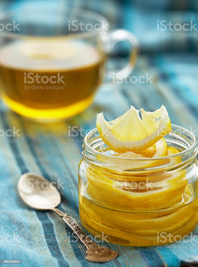 lemon with sugar is in a glass jar, next is a cup of tea royalty-free stock photo