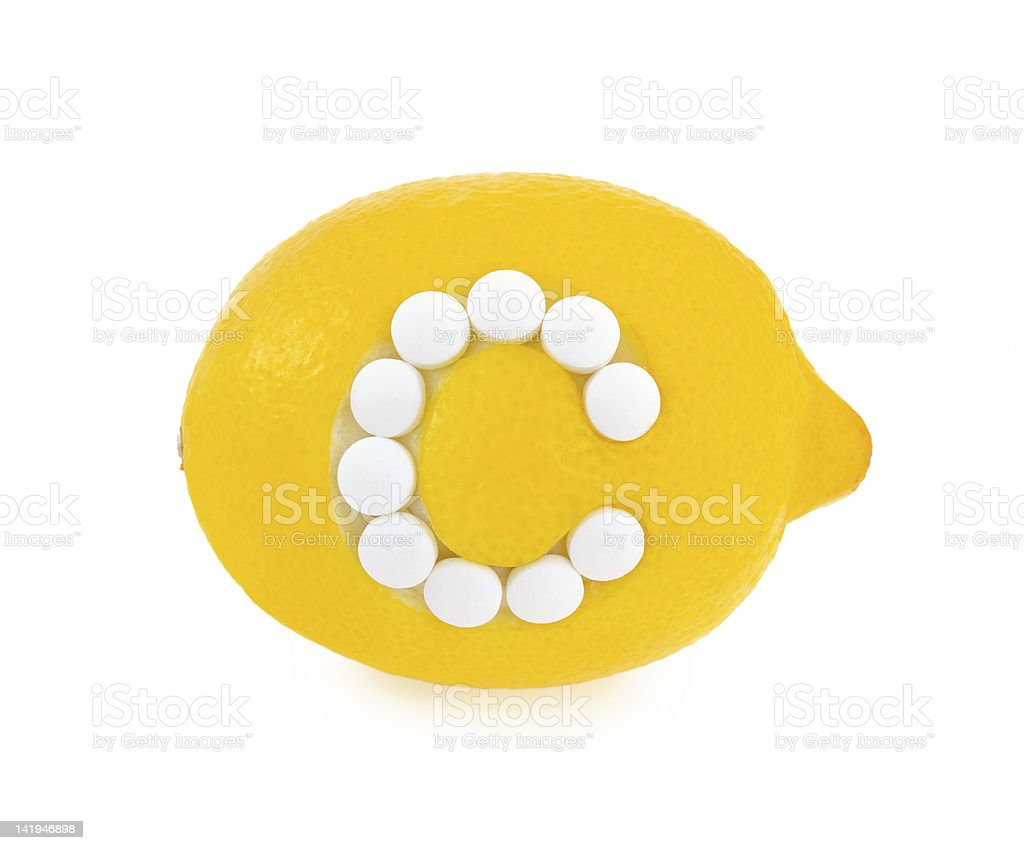 Lemon with vitamin c pills over white background - concept royalty-free stock photo