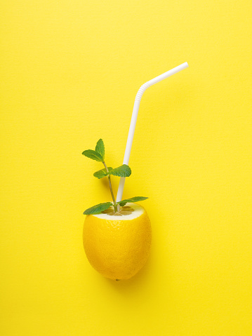 Lemon with white straw and mint on yellow background. Minimal styled creative summer concept. Imitation of a glass with lemonade.