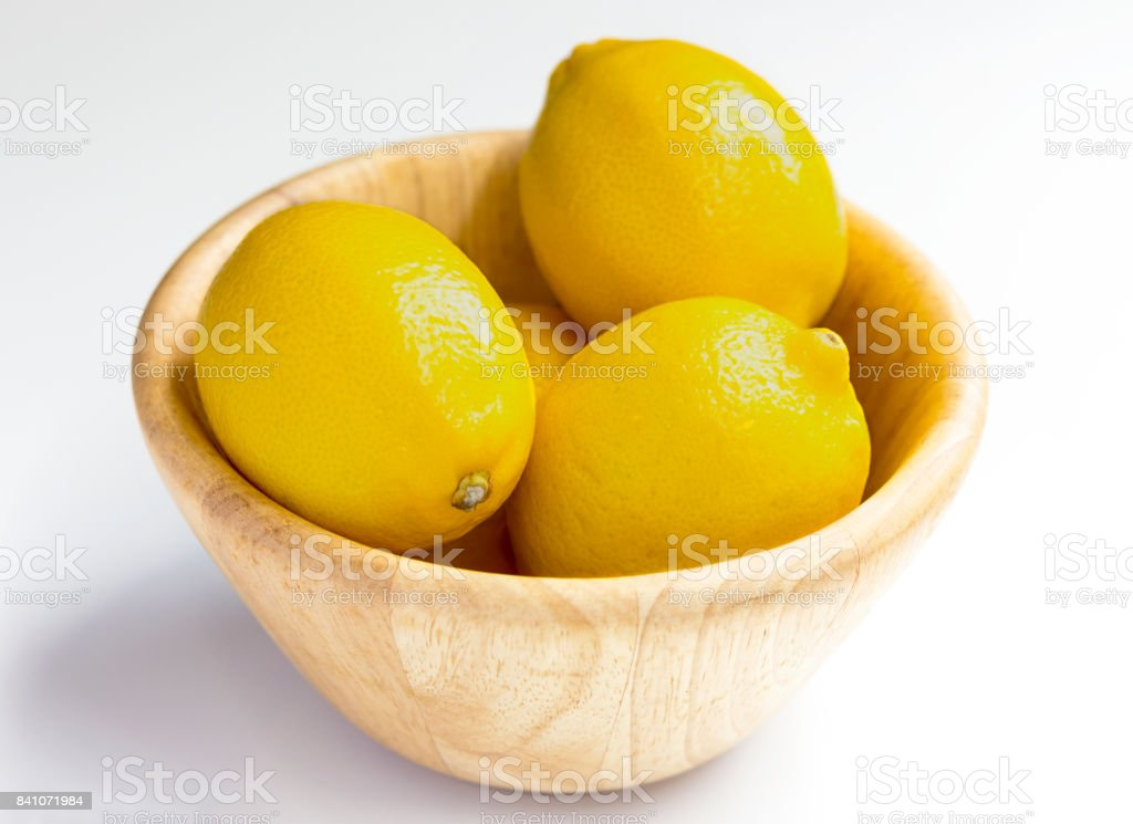 lemon with wooden bowl on white background. stock photo