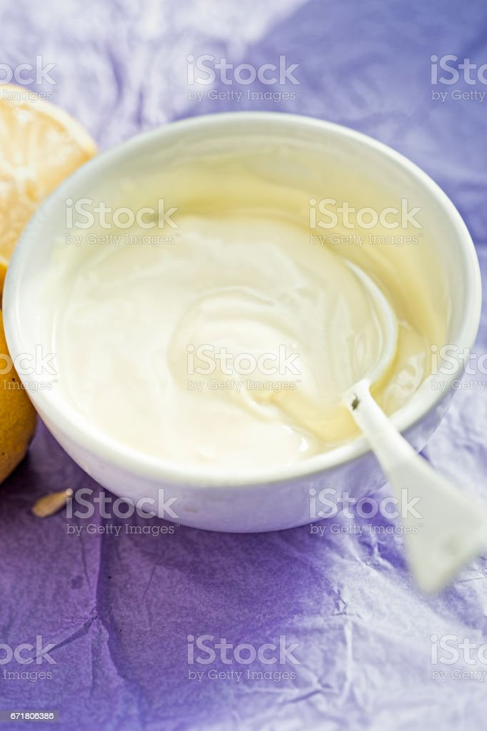Lemon yoghurt on violet background stock photo