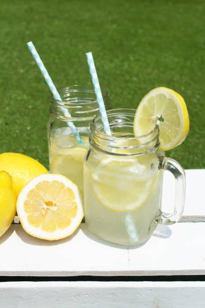 limonade glas mit zitrone und strohhalme - picknick tisch kühler stock-fotos und bilder