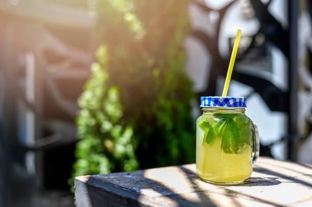 limonade glas mit zitronenspalten und strohhalme - picknick tisch kühler stock-fotos und bilder
