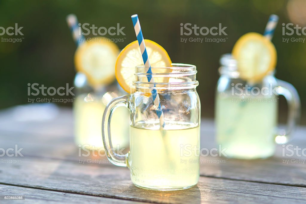 Lemonade glass jars with lemon wedges and straws stock photo