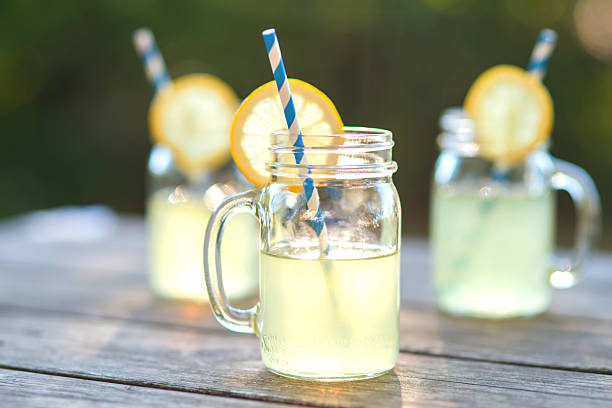 lemonade glass jars with lemon wedges and straws - limonade stock-fotos und bilder
