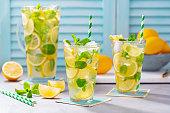 Lemonade, lemon, mint cocktail in glasses and jug. Blue background.
