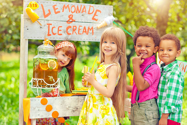 Lemonade stand and children Little girl selling lemonade from a lemonade stand outdoors in summer to children lemonade stand stock pictures, royalty-free photos & images