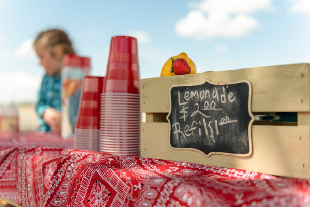 Lemonade stand and sign Focus on sign at lemonade stand. A lemon, strawberry and pile of red plastic cups in foreground. Out of focus girl in background. lemonade stand stock pictures, royalty-free photos & images