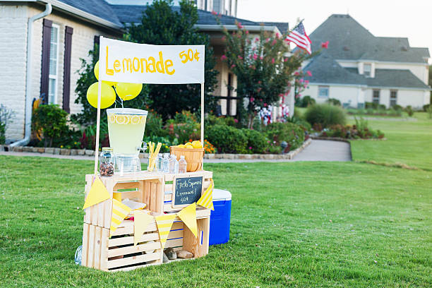 Lemonade stand set up in front yard A refreshing lemonade stand is set up in the front yard of a home in the suburbs on a sunny summer day. A beverage dispenser, basket of fresh lemons and glasses are on the stand. Balloons are attached to the stand. A banner across the top of the stand lists the price of the lemonade. lemonade stand stock pictures, royalty-free photos & images