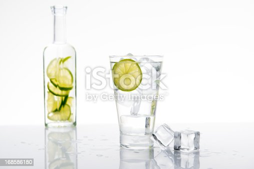 Cold glass of water, soda or an alcoholic drink with a slice of lime and ice cubes. A bottle with liquid and lime slices in the background.