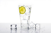 Cold glass of water, soda or an alcoholic drink with a slice of lime and ice cubes.