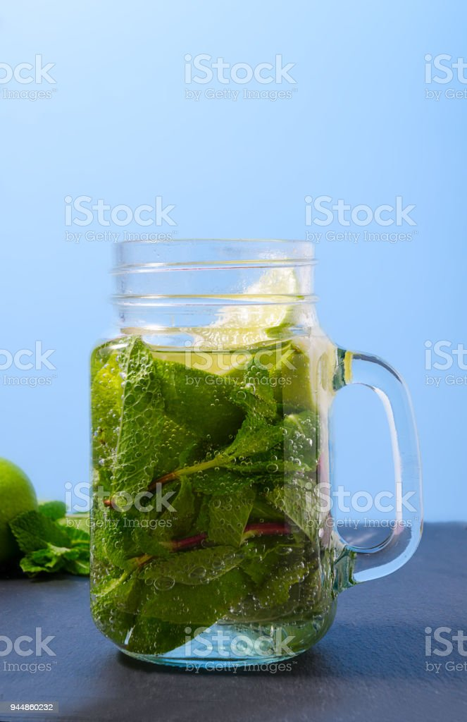 lemonade with lime and mint in a glass. Non-alcoholic refreshment drink. mojito in a glass with mint and lime. stock photo