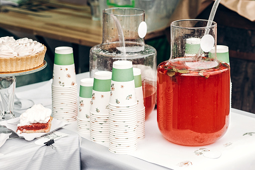lemonade with strawberry and mint in big glass jars and paper cups, space for text. street food festival. drink bar at reception, catering outdoors. summer picnic. colorful drinks