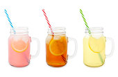 Pink and yellow lemonades and iced tea in jars isolated on white