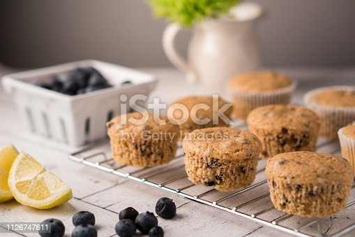 Fresh baked whole wheat lemon-blueberry muffins. Muffins cooling on a wire rack. Fresh blueberries and lemons on the table.