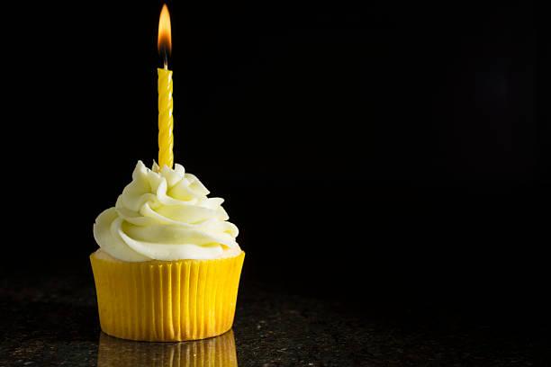 Lemon-Lime Cupcake with Candle on Black stock photo